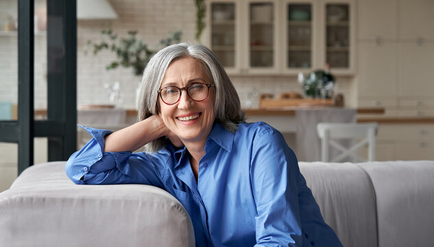 Happy relaxed mature old adult woman wearing glasses resting sitting on couch at home. Smiling middle aged grey-haired elegant senior lady relaxing on comfortable sofa looking at camera. Portrait.