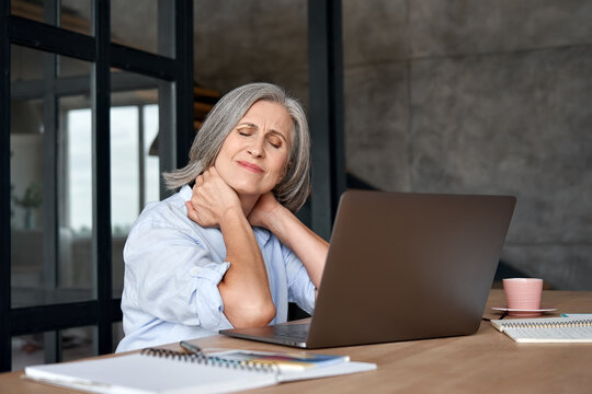 Tired stressed old mature business woman suffering from fibromyalgia neckpain working in office sitting at table. Overworked senior middle aged lady massaging neck feeling hurt pain from sedentary job