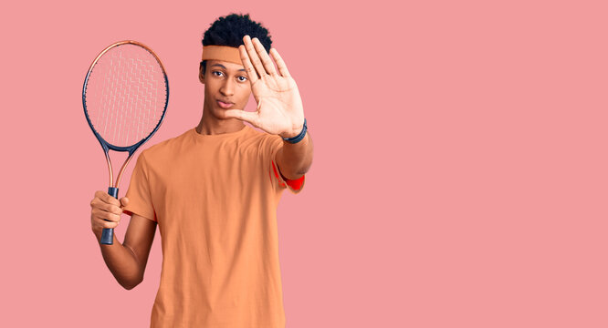 Young african american man playing tennis holding racket with open hand doing stop sign with serious and confident expression, defense gesture