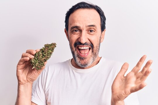 Middle age handsome man holding cannabis weed standing over isolated white background celebrating achievement with happy smile and winner expression with raised hand