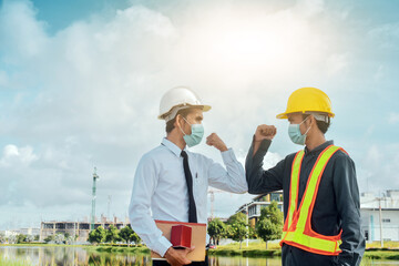 Engineers saluting each other by touching elbows,Two business people shake hand no touch outdoor on...
