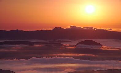 朝日が輝く遠くの山と低く漂う雲。オレンジ色の夜明けの風景。