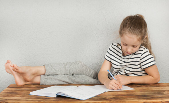 Girl 8 - 10 years old doing homework sitting at a wooden table. Homeschooling