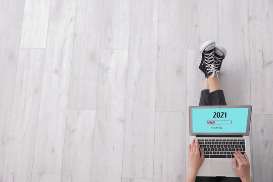 Young woman with laptop making to do list on 2021 year at home