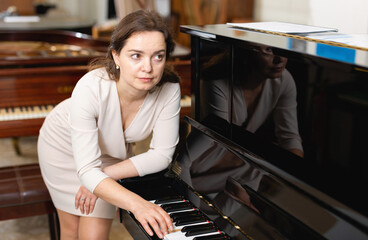 Beautiful girl chooses a piano in a music store. High quality photo