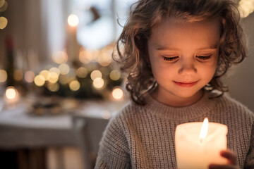 Photo sur Plexiglas Dinosaurs Cheerful small girl indoors at home at Christmas, holding candle.