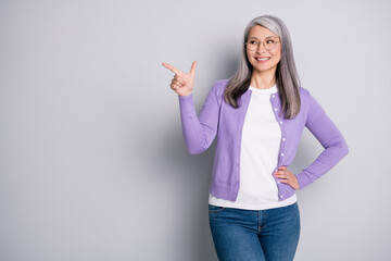 Wall Murals Height scale Photo portrait of positive satisfied grandmother smiling looking pointing showing at side with finger wearing jeans violet cardigan spectacles isolated on grey color background