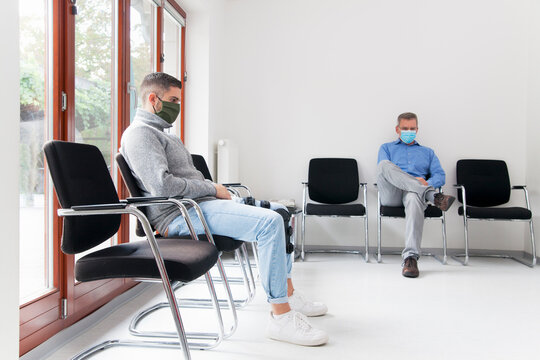 Young and mature man with face masks sitting in a waiting room of a hospital or office