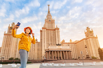Asian girl student studying at Moscow University and takes a selfie against the background of the main building.