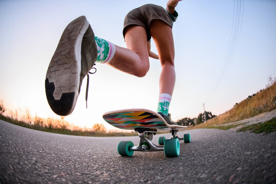 low angle view of girl who is riding on skateboard on the asphalt.