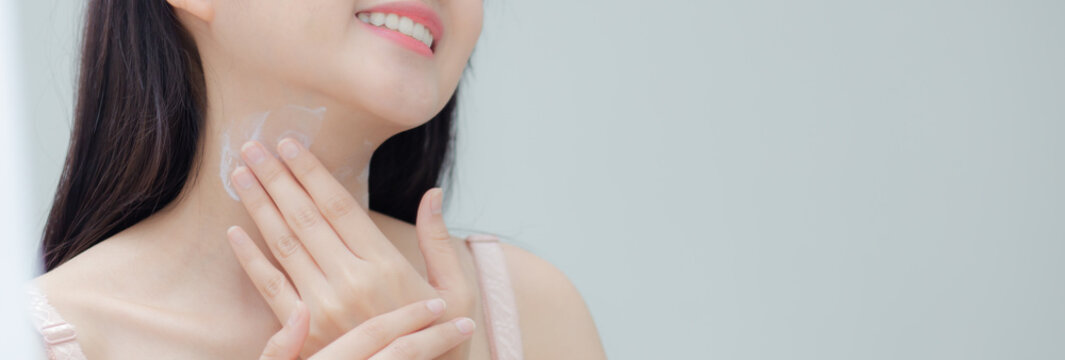Closeup beautiful young asian woman applying cream on neck and message, beauty girl applying lotion skin care for health and soft hydration, treatment and cosmetic with moisturizer, banner website.