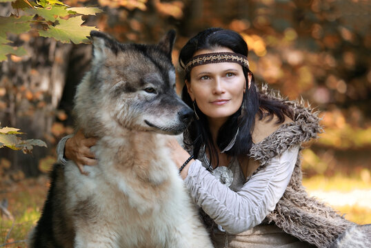 Portrait of a pretty woman with an Alaskan Malamute dog in the forest