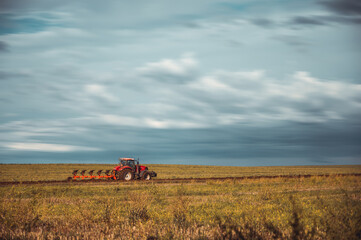 Tractor plowing the fields in the countryside. Agricultural tractor plowing the field. Red Tractor with plow.