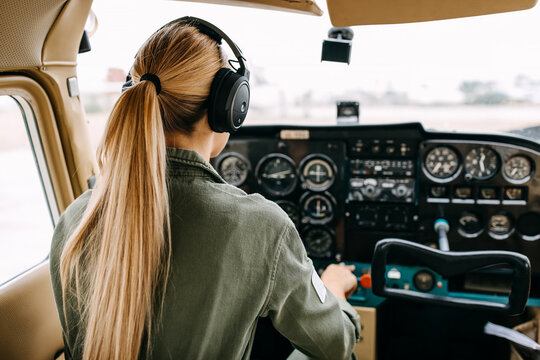 Back view over woman pilot flying an airplane, wearing headset.