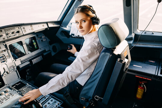 Serious woman pilot flying an airplane, sitting in cockpit.