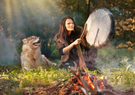 Shaman woman drumming in the sunny forest with an Alaskan Malamute dog