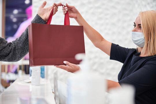 Responsible saleswoman in a mask holding a product bag