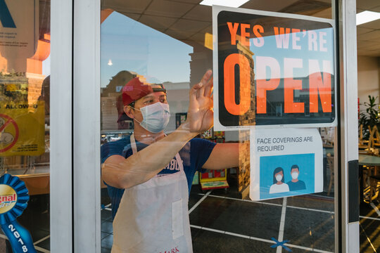 LOS ANGELES, UNITED STATES - Aug 02, 2020: Store employee posting an OPEN sign during covid-19 pandemic at S&S Donut, Los Angeles