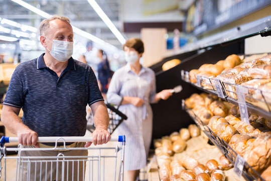 Senior man in protective mask with shopping trolley choosing pastries and products in supermarket