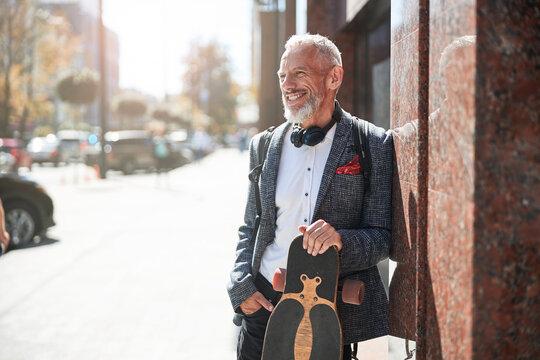 Positive elderly gentleman posing with a longboard