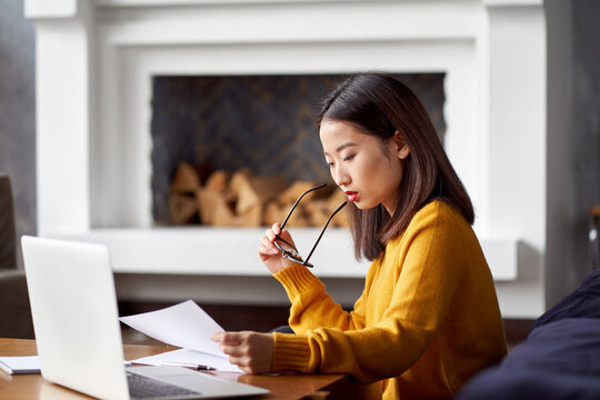 Asian woman working at home looking at documents. Beautiful Japanese female freelancer. Overworking, filling out papers, documents and reports