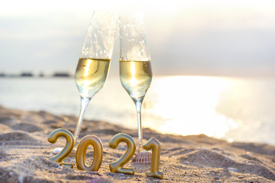 new year on the beach. Two glasses of champagne and the numbers 2021 standing on the sand against the sea background
