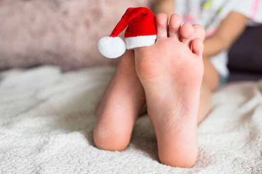 Kids foot with santa hat on big toe. Christmas barefoot concept with copy space