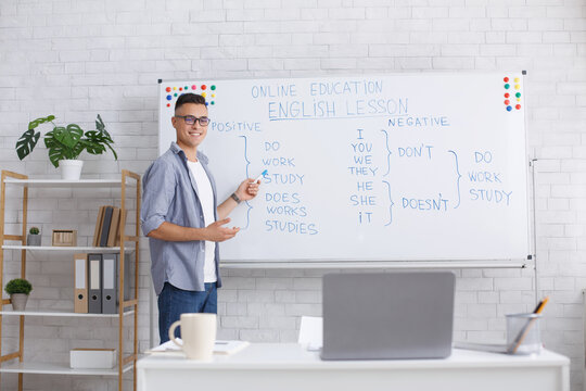 Lecture and lesson online, teacher at home and health protection. Smiling young guy with glasses explains rules of English language and records video on laptop webcam