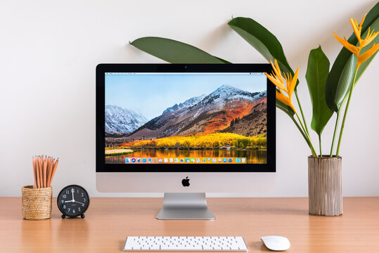 PHATTHALUNG, THAILAND - MARCH 24, 2018: iMac monitor computers, keyboard, magic mouse, pencils, clock and flowers vase on wooden table, created by Apple Inc.