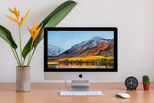 PHATTHALUNG, THAILAND - MARCH 24, 2018: iMac monitor computers, keyboard, magic mouse, clock, cactus and flowers vase on wooden table, created by Apple Inc.