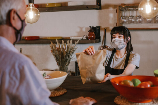 Caucasian waitress wearing protective face mask giving bag to customer in a restaurant. Young woman worker working with take away orders during corona virus outbreak. Concept food and drinks takeaway
