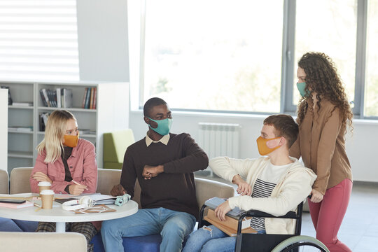 Side view at multi-ethnic group of students wearing masks while studying in college library with young man using wheelchair in foreground, copy space