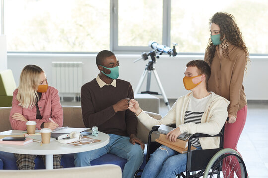 Portrait of multi-ethnic group of students wearing masks while studying in college library with young man using wheelchair in foreground, copy space
