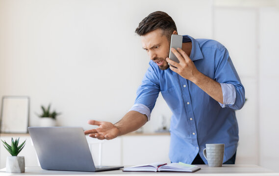 Problems At Work. Angry Businessman Talking On Cellphone, Having Troubles With Computer