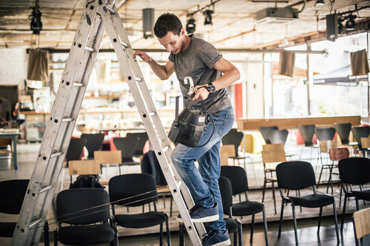 Behind the scene Lighting technician electric engineer adjusting stage lights. Spotlights in the theater