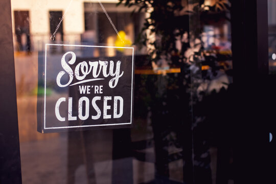 Vintage sorry we are closed sign hanging on a glass door.