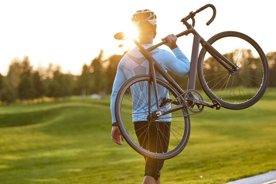 Strong athletic man in sportswear carrying his bicycle and watching amazing sunset after cycling in park