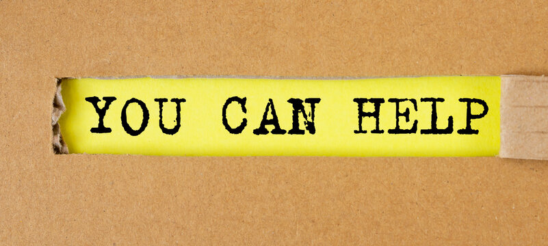 You Can Help inscription text on craft paper on yellow table through torn craft paper