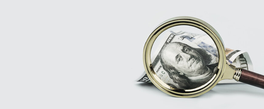 One hundred dollars note under magnifying glass on grey background banner. Finance markets. investments loans earnings concept. Personal accounting debts and credits bankruptcy with copy space