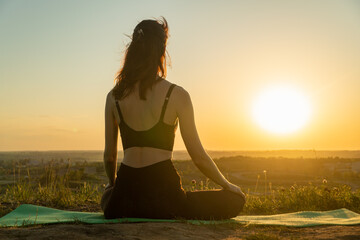 Young woman meditating in a yoga lotus pose on nature at sunset. Concept of healthy lifestyle and relaxation