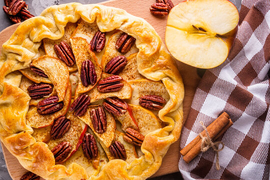 crispy apple galette with pecans on a rustic wooden background