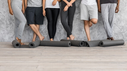 Diverse People In Sportswear With Yoga Mats In Hands Posing Near Wall