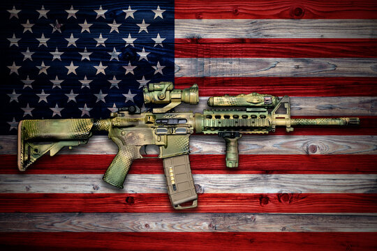 Camo painted army carbine on wooden surface with USA flag