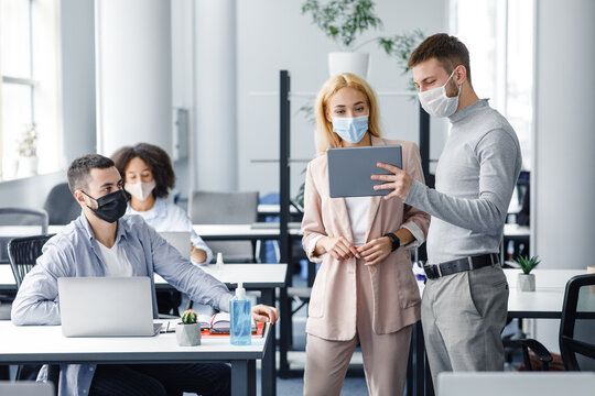 Teamwork in corporate company and social distance during coronavirus epidemic. Male manager in protective mask shows tablet to workers in interior