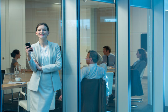 Portrait happy businesswoman with smart phone at office window