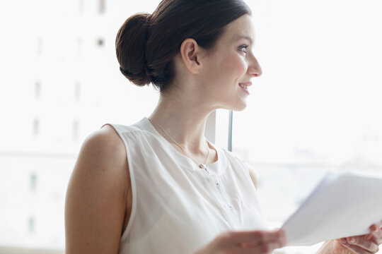 Smiling young corporate businesswoman in window