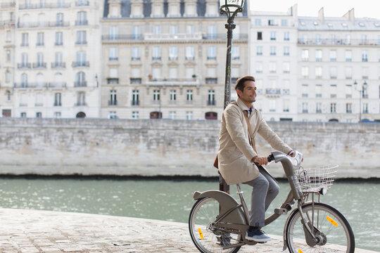 Businessman riding rented bicycle along Seine River, Paris, France