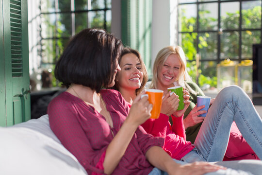 Happy young women friends drinking tea on sofa