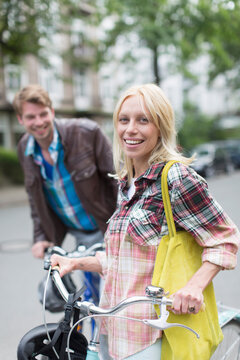 Portrait young couple with bicycles on street