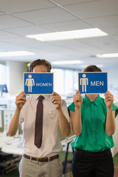 Business people holding men and women bathroom signs